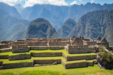 Photography taken from Machu Picchu ruins where big walls made of stones can be appreciated. Behind, big and beautiful mountains. Peru.