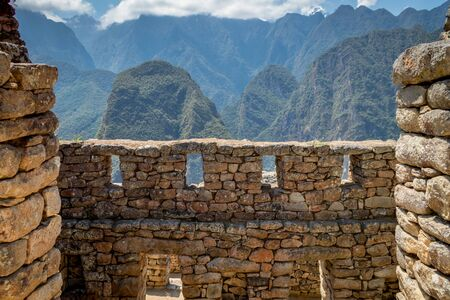 Machu Picchu shot taken fron the inside of a ruin where big walls made of stones and windows can be appreciated. There are huge mountains on the background. Machu Picchu, Peru Stock fotó