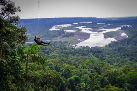 Tourist having fun in the air held by a rope. Fabulous Amazonian landscape where you can appreciate the immensity of the jungle and a huge river. Stock Photo