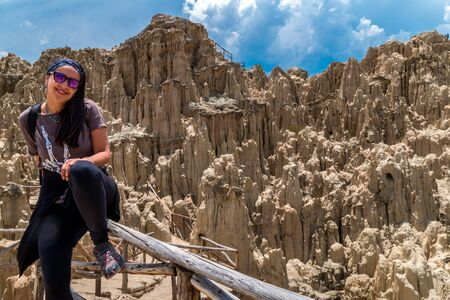 A tourist woman posing in the Moon Valley in La Paz, Bolivia. Many clay peaks can be seen on the background 스톡 콘텐츠