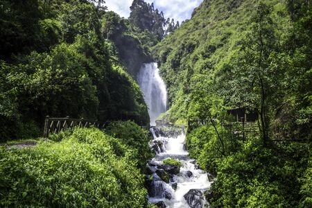 View of Peguche Waterfall in the mountains of Ecuador. Its surrounded by green forest full of vegetation