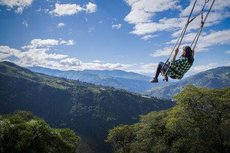 Woman on the swing of the end of the world in Ba? ? os, Ambato. The tree house, Ecuador, Latin America