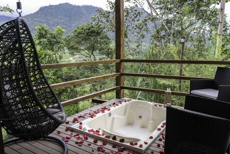 Outdoor Jacuzzi bathtub on hotel balcony with mountain view. Pink petals are seen surrounding and some armchairs in the place