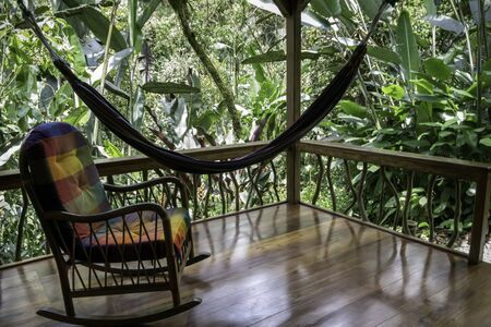 Porch of a house in the jungle. There is a colorful rocking chair and a Paraguayan hammock. The completely wooden construction