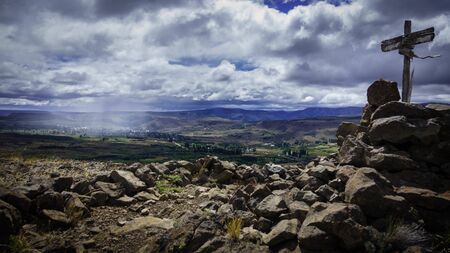 Beautiful Patagonian Landscape where you can see a village in the distance and a cross surrounded by rocks on the right. Sky full of clouds