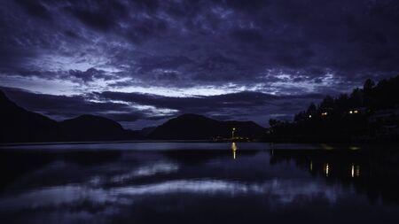 Blaue Stunde im Dock von Caleta Tortel. Die Pazifikküste kann geschätzt werden. Es gibt einige Figuren von Fjorden, auch Lichter und Rauch aus einem Schornstein. Patagonien, Chile.