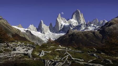 Blick auf El Chalten (auch bekannt als Fitz Roy). Der Mond am Himmel kann geschätzt werden. Auf dem Boden einige getrocknete Stämme. Herbst in Patagonien Argentinien Standard-Bild