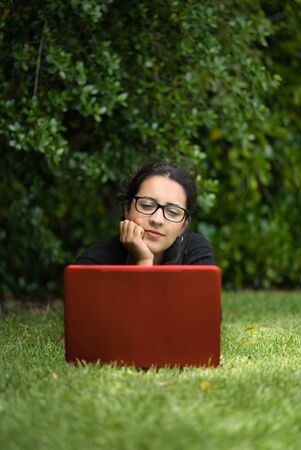 Woman lying down on the grass of a park looking at the screen her laptop. She seems to be thinking about something. Natural Environment. Vertical Photography