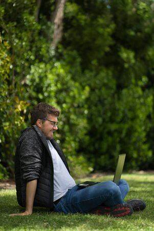 Young man looking at his computer in a park. He is sitting on the green grass and seems having fun. Natural Environment. Vertical Photography Foto de archivo