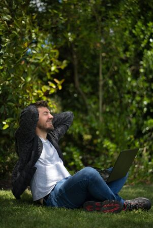 Young man sitting on the grass of a park with his laptop while he has his hands behind his head like he is stretching and relaxing. Natural Environment. Vertical Photography