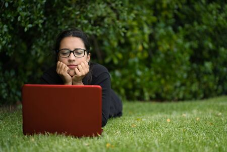 young woman lying down on the grass of a park while watching the screen of her laptop. Natural Environment. Technological concept Foto de archivo