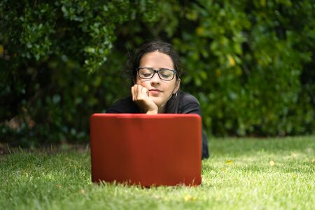Woman lying down on the grass of a park looking at the screen her laptop. She seems to be thinking about something. Natural Environment. Technological concept
