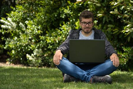 Caucasian man sitting on the grass of a park and looking at the screen of his laptop. Natural Environment. Technological concept