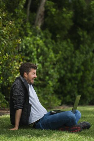 Caucasian man laughing while he is looking at his laptop. He is sitting on the grass of a park.Vertical Photography