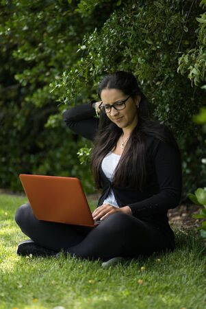 Brunette woman sitting on the grass with her laptop. She is with her legs crossed and she has an expression of uncertainty. Natural environment. Vertical photography