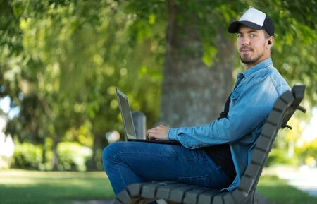 Young man wearing cap listening to music with wireless earbuds and laptop. He is sitting on a park bench