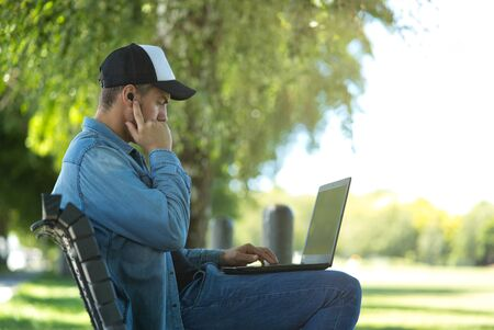 Young man wearing a cap listening to music with wireless earbuds and his laptop on outdoor background