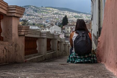 A woman sitting on old stairs of the old town of Quito, Ecuador. She is with her back turned and a beautiful mount landscape of the village can be seen behind.