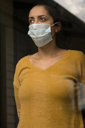 Brunette young woman wearing face mask looking out the window, self isolated at home. Corona virus and Quarantine concept. Vertical
