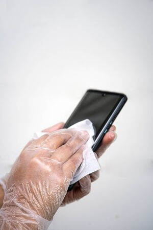 Hand wearing sanitary gloves cleaning mobile phone. close up. White background. Covid-19 concept Foto de archivo