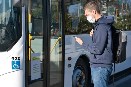 Young caucasian man wearing face mask and looking at mobile while taking the bus during pandemic covid-19. Health and care concept Foto de archivo