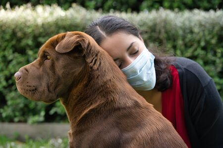 Young woman hugging a shar pei dog wearing a face mask on the garden. Covid-19 and quarantine concept