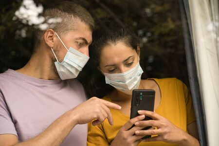 Couple wearing face mask standing in front of the window and watching at smartphone at home. Coronavirus and Quarantine concept Foto de archivo