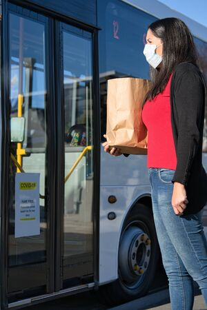 Young hispanic woman wearing face mask about to take the bus after shopping during pandemic coronavirus. Vertical photography Foto de archivo