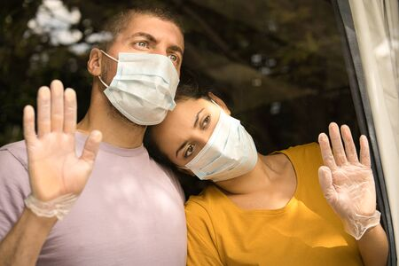 Young couple wearing face mask and sanitary gloves in front of the window and cuddling each other. Coronavirus and Quarantine concept