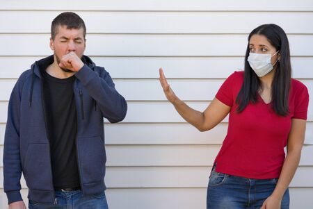 Man coughing next to a worried woman wearing face mask. Coronavirus concept