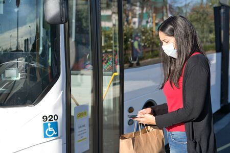 Young brunette woman wearing face mask at the bus stop while holding bag and mobile. Coronavirus concept