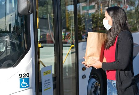 Latin woman wearing face mask and holding a shopping bag at the bus stop during pandemic covid-19. Coronavirus concept Foto de archivo