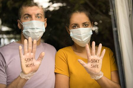Couple wearing face masks and sanitary gloves that says ¨Stay home, stay safe