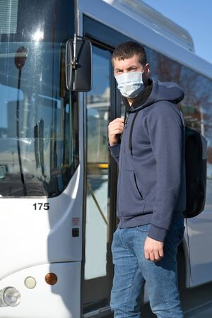 Young caucasian man wearing face mask about to take the bus at the bus station. Covid-19 concept. Vertical photography Foto de archivo