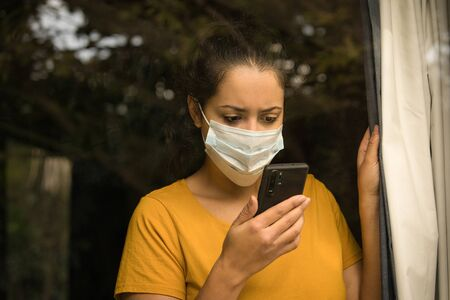 Latin woman wearing a face mask looking at her smartphone, self isolated at home. COVID-19 and Quarantine concept. Foto de archivo