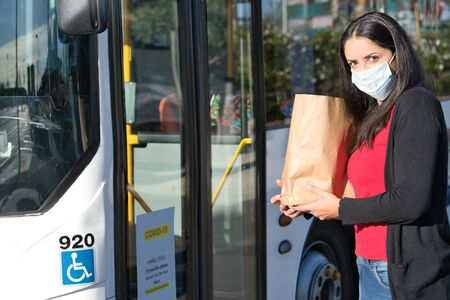 Hispanic woman holding shopping bag and wearing face mask against coronovarius about to take the bus. Health and care concept Foto de archivo