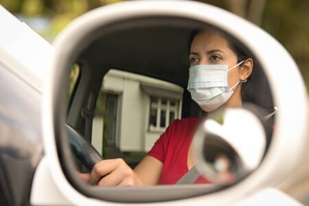Brunette woman wearing face mask driving her car through the side mirror car. Covid-19 (Corona virus) concept Foto de archivo