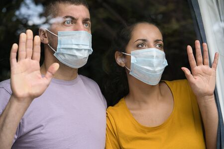 Young couple wearing face masks and looking out through the window at home. Coronavirus and Quarantine concept Foto de archivo