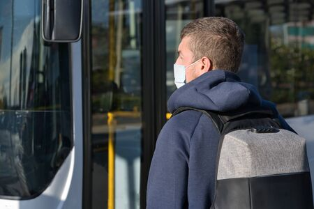 Man backwards wearing face mask and backpack about to take the bus at the bus station. Covid-19 concept
