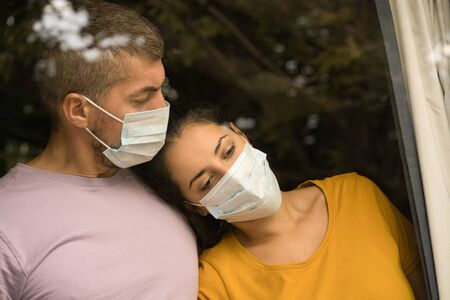 Young couple wearing face mask in front of the window and cuddling each other at home. Coronavirus and Quarantine concept Foto de archivo