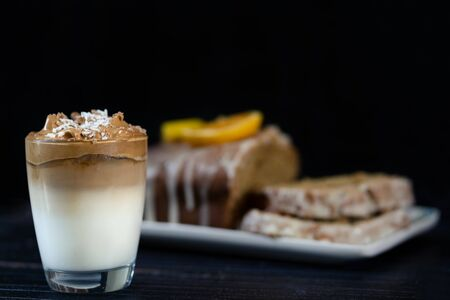 Iced Dalgona coffee on a glass and a wholemeal orange cake behind. A trendy whipped coffee decorated with coconut and chocolate. Black background Foto de archivo
