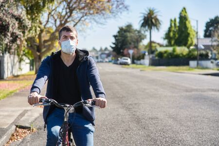 young caucasian man wearing face mask and riding his bicycle on the street. COVID-19 concept