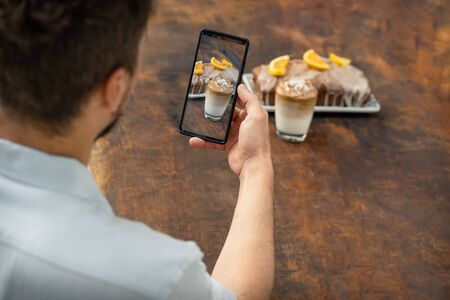 Man taking a photo with mobile at a glass of Dalgona coffee and an orange cake on a wooden background