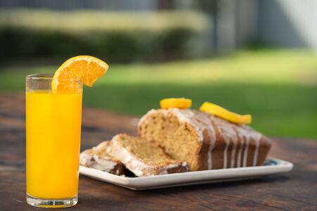 Fresh orange juice on a glass with an orange wholemeal cake behind. Outdoor background