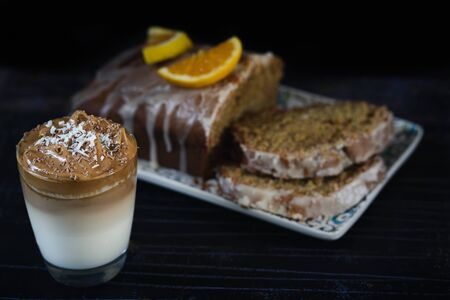 Glass of Dalgona coffee served on a glass and a orange cake behind. A trendy whipped coffee. Black background