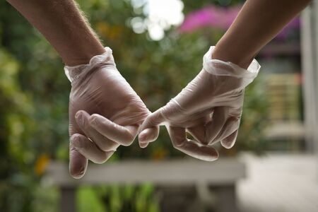 Hands holding each other with the little finger wearing sanitary gloves. Close up. COVID-19 concept Foto de archivo