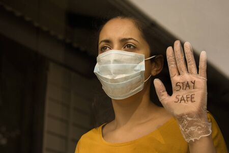 young brunette woman wearing face mask and sanitary glove that says