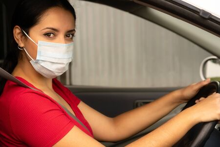 Young hispanic woman wearing face mask driving her car and looking at the camera. Covid-19 (Corona virus) concept