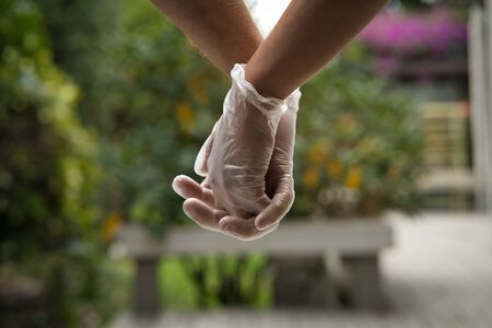 Hands holding each other wearing sanitary gloves. Close up. COVID-19 concept Foto de archivo
