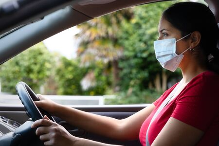 Young hispanic woman wearing face mask driving her car. Covid-19 (Corona virus) concept